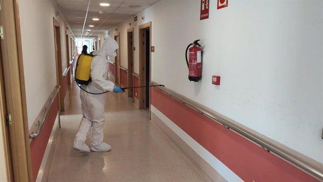 Un miembro de la UME desinfectando.
