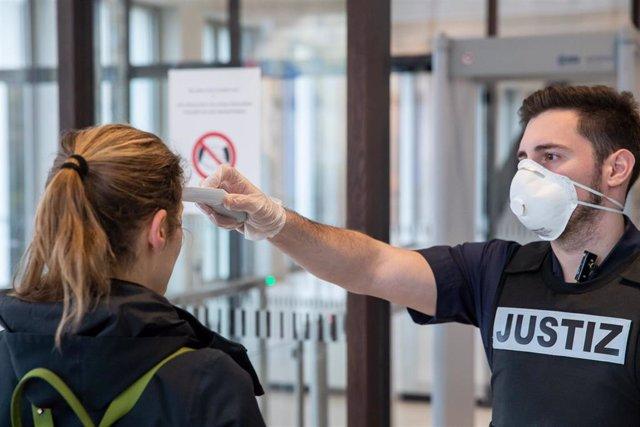 Un empleado de un tribunal de Nuremberg toma la temperatura a una visitante