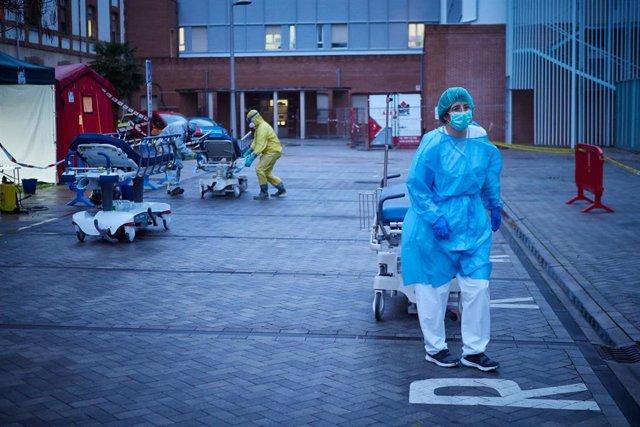 Varios voluntarios de DYA Navarra trasladan una de las camillas utilizadas en las ambulancias del servicio de Urgencias del Hospital de Navarra para llevar a pacientes infectados con coronavirus durante la tercera semana de Estado de Alarma