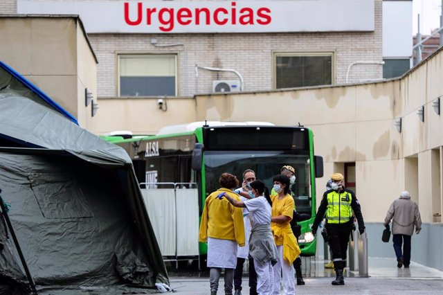 Un grupo de sanitario habla al lado de los policías militares de la UME que durante la jornada de hoy escoltan salida desde donde parte los autobuses de transporte público que están siendo utilizados para trasladar pacientes contagiados con coronavirus