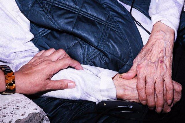 Una mujer cuidadora atiende a un anciano