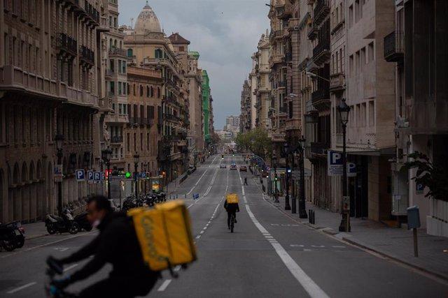 Dos trabajadores de Glovo en bicicleta por una calle de Barcelona, el primer día laborable de la segunda semana desde que se decretó el estado de alarma en el país a consecuencia del coronavirus, en Barcelona/Catalunya (España) a 23 de marzo de 2020.