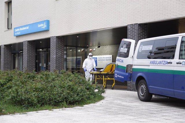 Un sanitario protegido con un traje, guantes y mascarilla, saca una camilla de una ambulancia en la entrada a la residencia, en Vitoria/Euskadi (España) a 18 de marzo de 2020.