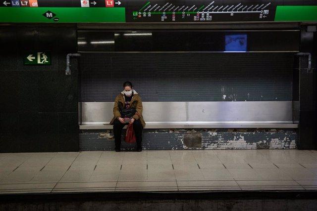 Una dona protegida amb mascarilla espera asseguda en un banc de l'andana al fet que arribi el metre, a Barcelona/Catalunya (Espanya) a 26 de març de 2020.
