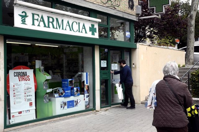 Un hombre entra en una Farmacia, abierta por ser esencial, el día en el que entra en vigor la limitación total de movimientos salvo de los trabajadores de actividades esenciales, medida adoptada ayer por el Gobierno como prevención del coronavirus duran