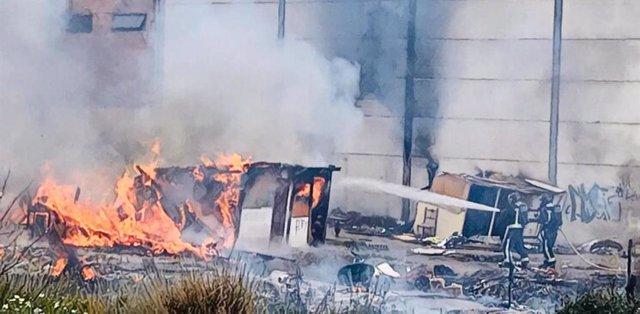 Intervención de los bomebros sodocando el fuego en el asentamiento chabolista abandonado