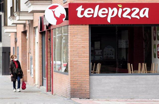Una mujer protegida con mascarilla pasea cerca de un local de Telepizza el mismo día en el que han comenzado a servir menús para alumnos madrileños con beca comedor y así evitar que les falten alimentos por la crisis del coronavirus, en Madrid.