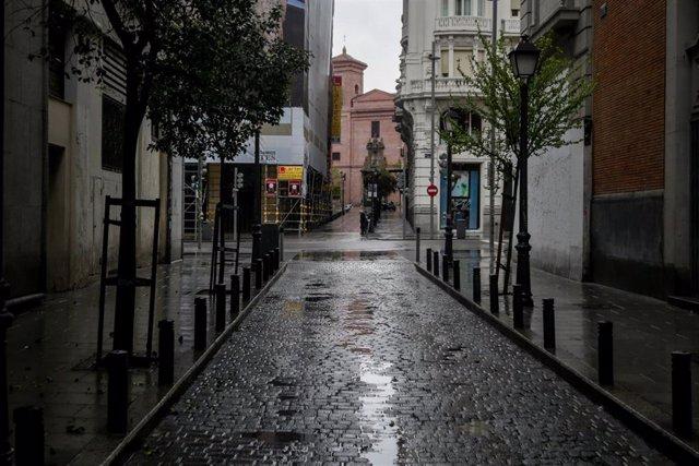 Una céntrica calle de Madrid vacía donde las temperaturas han bajado estrepitosamente durante el segundo día de la entrada en vigor de la limitación total de movimientos salvo de los trabajadores de actividades esenciales, medida adoptada ayer por el Gobi