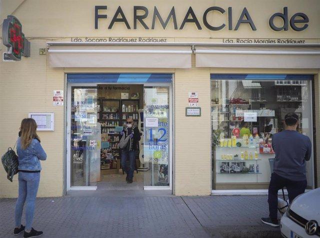 Un hombre compra en una farmacia, abierta por ser esencial, durante la limitación total de movimientos salvo de los trabajadores de actividades esenciales, medida adoptada por el Gobierno como prevención del coronavirus durante el estado de alarma