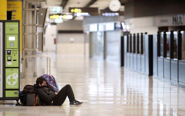 Un pasajero espera tumbado sobre su equipaje en la Terminal 4 del Aeropuerto Adolfo Suárez Madrid-Barajas un día después de efectuar el cierre total de las demás terminales del aeropuerto.