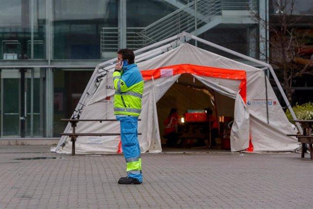 Un técnico de SUMMA-112 habla por teléfono junto a una carpa del SUMMA en el exterior del Hospital temporal de la Comunidad de Madrid habilitado en IFEMA para pacientes con coronavirus, en Madrid (España)