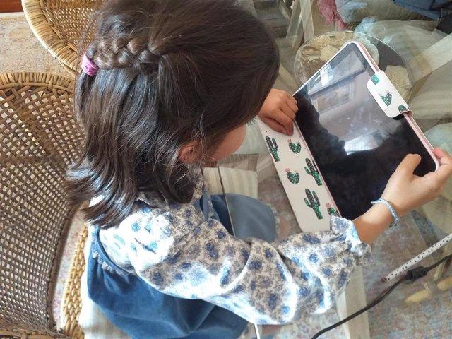 Una escolar haciendo deberes desde casa de forma telemática.