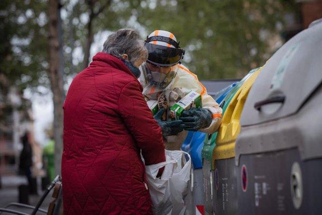 Un treballador que desinfecta i neteja els contenidors d'escombraries de Barcelona ajuda una dona durant la tercera setmana de confinament per la crisi del coronavirus. (arxiu)
