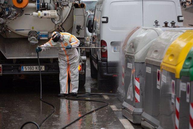 Un trabajador desinfecta y limpia los contenedores de basura de Barcelona durante la tercera semana de confinamiento