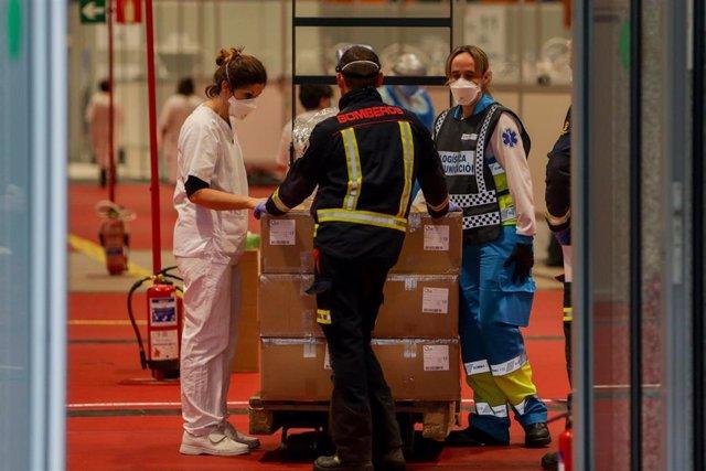 Una enfermera, un bombero y un técnico sanitario conversan en el interior del hospital Temporal de la Comunidad de Madrid en IFEMA para pacientes con Covid-19, en Madrid el 31 de marzo de 2020.