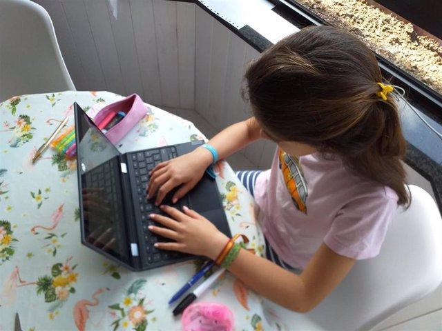 Una niña, haciendo deberes en casa con el ordenador portátil.