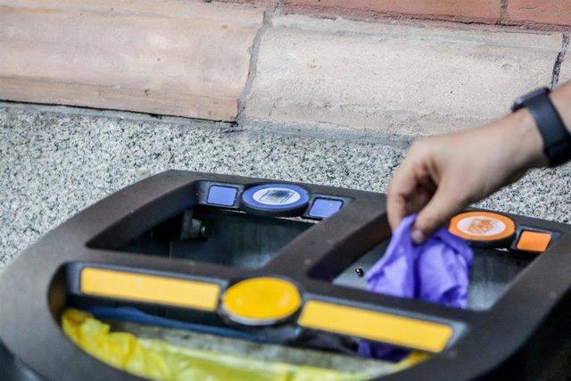 Una persona deposita un guante de látex utilizado en los hospitales españoles