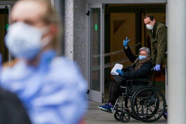 Un familiar recoge a una paciente con coronavirus que abandona el Hospital temporal de la Comunidad de Madrid habilitado en IFEMA tras superar el Covid-19