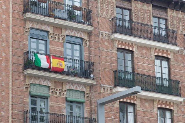 Balcón con las banderas de Italia y España, durante el primer día laborable de la segunda semana desde que se decretó el estado de alarma en el país a consecuencia del coronavirus, en Madrid (España), a 23 de marzo de 2020.