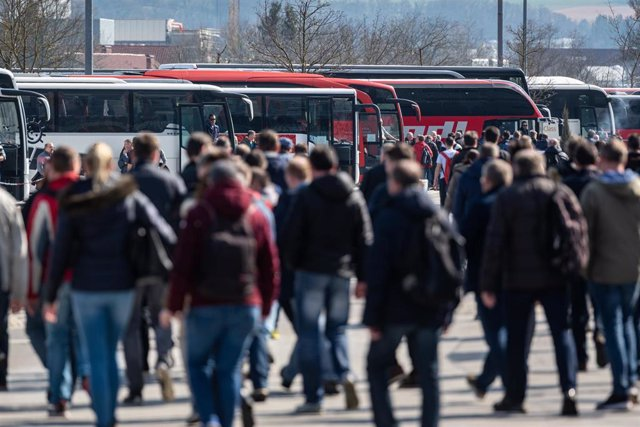 18 March 2020, Bavaria, Dingolfing: BMW employees walk in front of buses during the shift change at the plant. BMW stops car production in its European plants and in South Africa for four weeks due to the coronavirus crisis. Photo: Armin Weigel/dpa