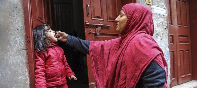 Una trabajadora sanitaria vacuna a una niña de 4 años contra la polio en la puerta de su casa en el área de Lahore, en Pakistán.