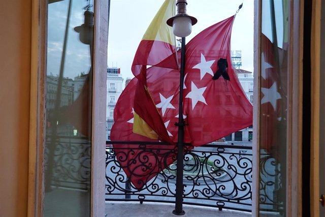 Vista desde el interior de las dependencias de la sede de la Comunidad de Madrid en la Puerta del Sol, con las banderas a media asta y un crespón negro en la bandera regional por los fallecidos por coronavirus, después de que la Comunidad de Madrid haya c