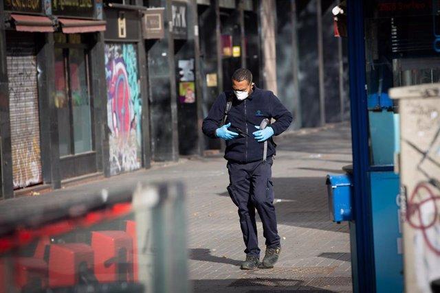 Un hombre protegido con mascarilla y guantes camina por una calle durante el estado de alarma del coronavirus en Barcelona