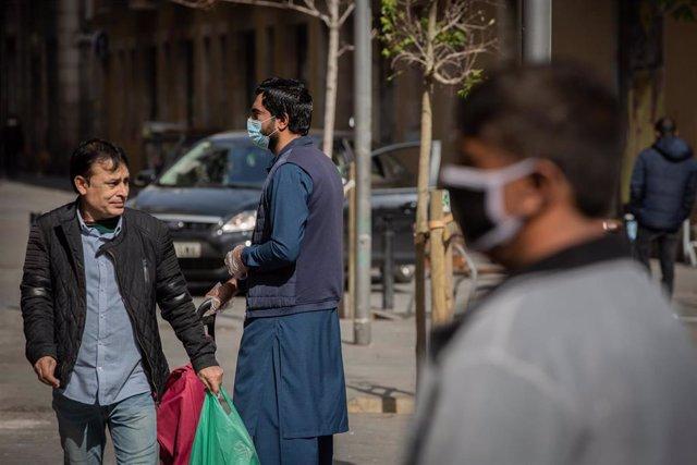 Varias personas protegidas con mascarillas durante el primer día laborable de la segunda semana desde que se decretó el estado de alarma en el país a consecuencia del coronavirus, en Barcelona/Catalunya (España) a 23 de marzo de 2020.