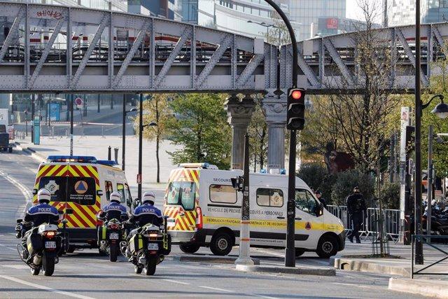 01 April 2020, France, Paris: Police escort two ambulances