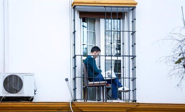 Un ciudadano aprovecha su minúsculo balcón para leer en la tercera semana de confinamiento por el coronavirus COVID 19. Sevilla a 03 de abril del 2020