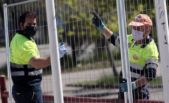 Dos operarios protegidos con mascarilla verjan las zona exteriores pertenecientes al Palacio de Hielo de Majadahonda donde la Comunidad de Madrid trabaja durante el día de hoy, con el Ayuntamiento de Majadahonda