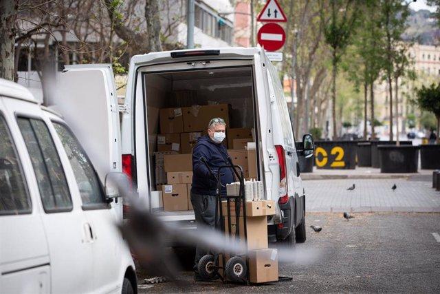 Un hombre protegido con mascarilla trabaja de repartidor durante el noveno día laborable desde que se decretó el estado de alarma en el país a consecuencia del coronavirus, en Barcelona/Catalunya (España) a 26 de marzo de 2020.