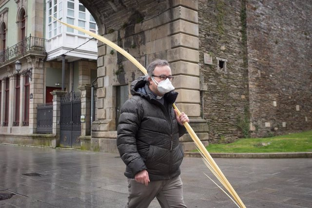 Un cura camina con una palma bendecida durante el Domingo de Ramos en Lugo tras la suspensión de la Semana Santa por el estado de alarma del coronavirus, en Lugo/Galicia (España) a 5 de abril de 2020