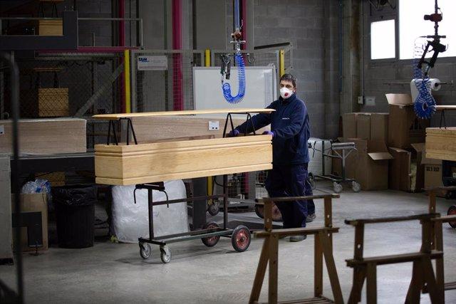 Un treballador de l'empresa Eurocoffin, la fbrica de taüts de Serveis Funeraris de Barcelona - Grup Mémora, situada a la muntanya de Montjuc de Barcelona, treballa amb la fusta d'un dels seus taüts durant la seva jornada laboral.