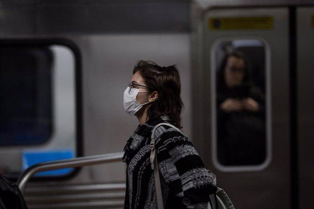 Mujer con mascarilla en el metro de Sao Paulo por el brote del nuevo coronavirus