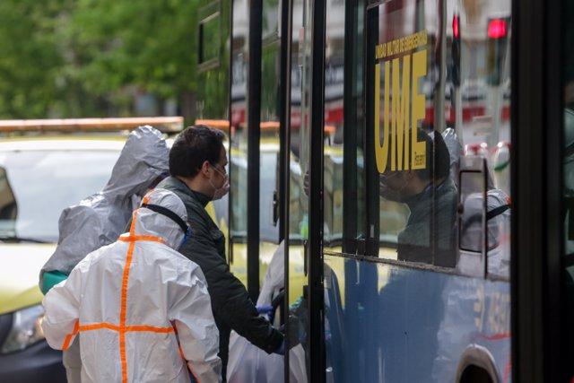 Dos sanitarios ayudan a un enfermo leve de Covid-19 a subir a un autobús