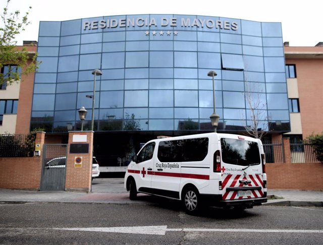 Un coche y una furgoneta de la Cruz Roja llegan a la Residencia de Mayores Los Ángeles, en Getafe (Madrid).