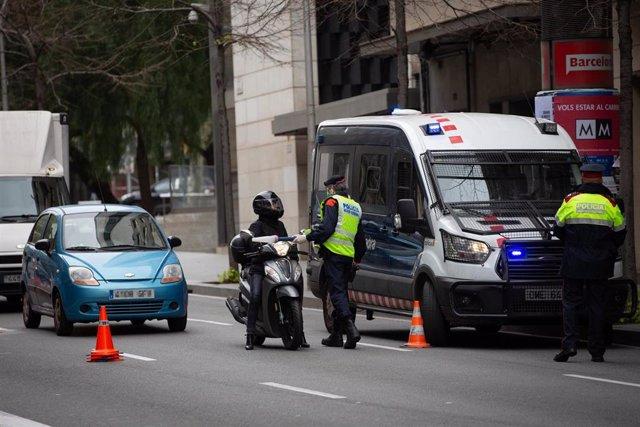 Dos Mossos d'Esquadra en un control de tráfico en la calle Balmes con la Avenida Diagonal de Barcelona para vigilar que se cumplen las medidas de confinamiento, en Barcelona/Catalunya (España) a 31 de marzo de 2020.