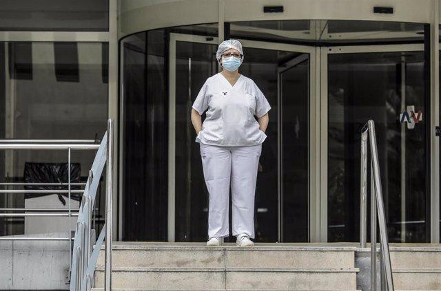 Sanitaria protegida con mascarilla y gorro durante el minuto de silencio en la entrada del Hospital Doctor Peset por la técnica de enfermería fallecida por coronavirus, en Valencia/Comunidad Valenciana (España) a 6 de abril de 2020.