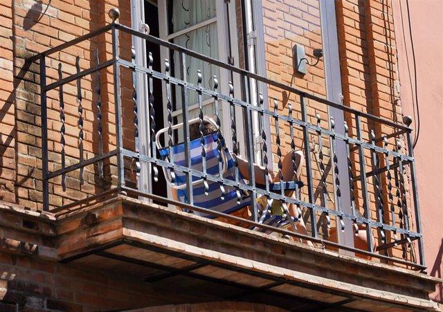 Un joven aprovecha su minúsculo balcón para tomar el sol en la tercera semana de confinamiento por el coronavirus COVID 19. Sevilla a 03 de abril del 2020