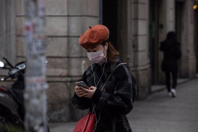 Una mujer con mascarilla en el Norte de Italia usando un smartphone durante el brote de coronavirus