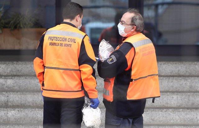 Dos agentes de Protección Civil de Boadilla del Monte protegidos con mascarillas llevan mascarillas a la Residencia de Mayores Los Ángeles en Getafe para la protección contra el coronavirus, en Getafe (Madrid) a 6 de abril de 2020.