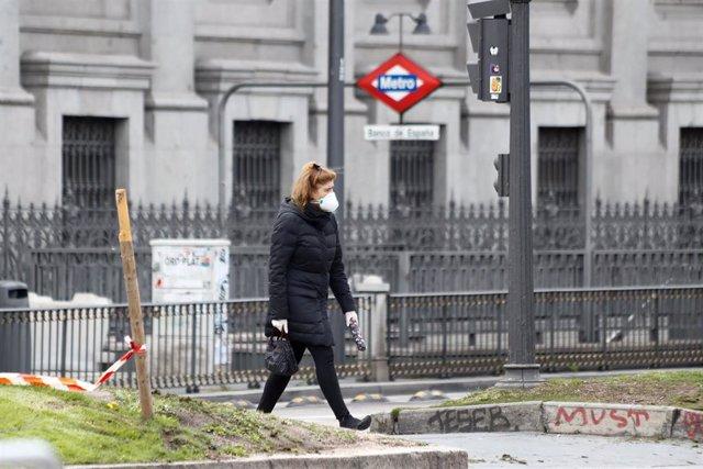 Una mujer con mascarilla pasea junto a la boca del metro de Banco de España durante el primer día de la cuarta semana de estado de alarma decretado por el Gobierno para combatir el coronavirus, en Madrid (España) a 6 de abril de 2020.