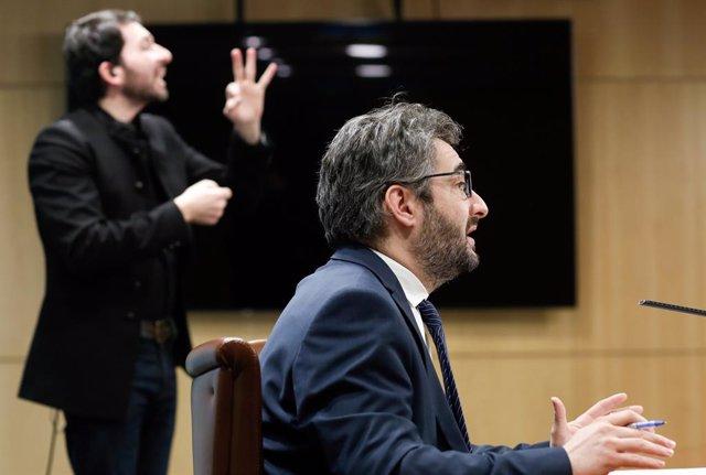 El ministre Portaveu, Eric Jover, en primer plànol, i l'intèrpret del llenguatge dels signes, David Jiménez, al fons.