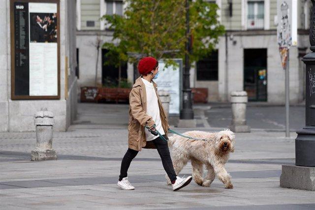 Una mujer pasea a su perro durante el primer día de la cuarta semana de estado de alarma decretado por el Gobierno para combatir el coronavirus, en Madrid (España) a 6 de abril de 2020.