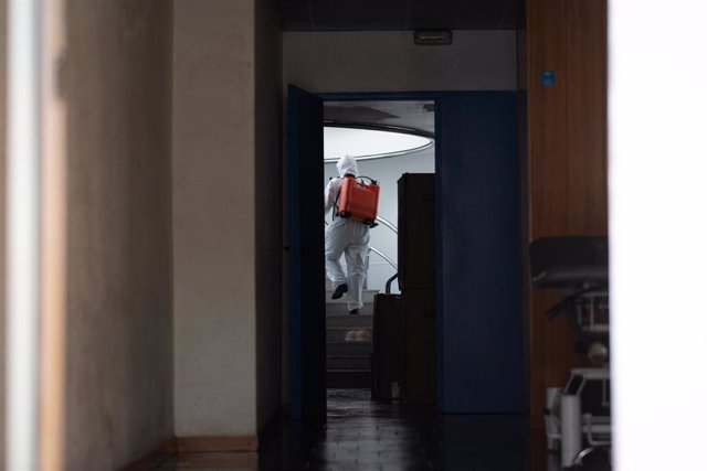 Un militar de la UME con traje de protección desinfecta espacios de una residencia geriátrica en Barcelona