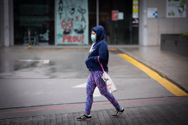 Una mujer pasa por las inmediaciones de la Estación de Barcelona Sants durante el día en el que entra en vigor la limitación total de movimientos salvo de los trabajadores de actividades esenciales, medida adoptada ayer por el Gobierno como prevención del