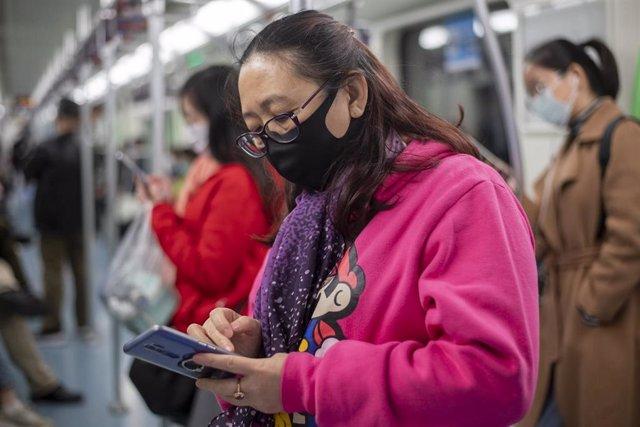 Una mujer se protege con una mascarilla durante su viaje en el metro de Shanghai.