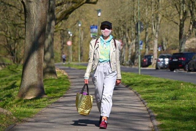 Una mujer pasea con mascarilla en Alemania