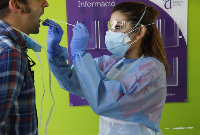06 April 2020, Spain, Palma: A health care worker takes a sample from a patient in the Establiments district for a coronavirus test. The Balearic Ministry of Health has set up a new COVID Express unit for sampling in the health sector.